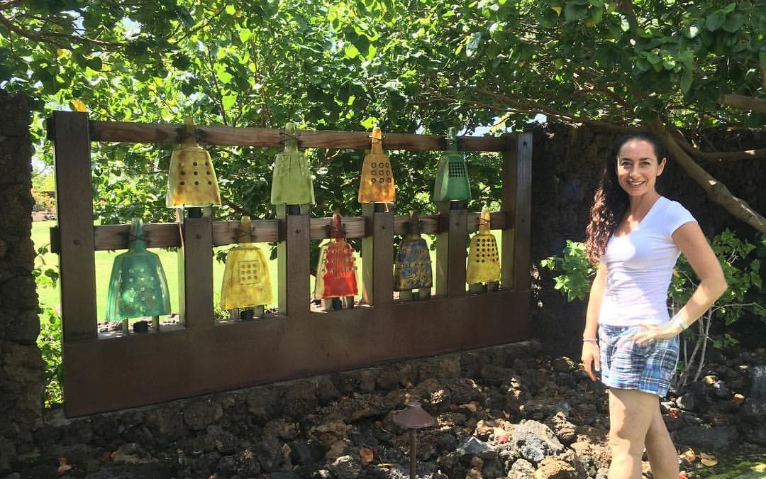 Marlene Rose outdoors with her cast glass bell wall